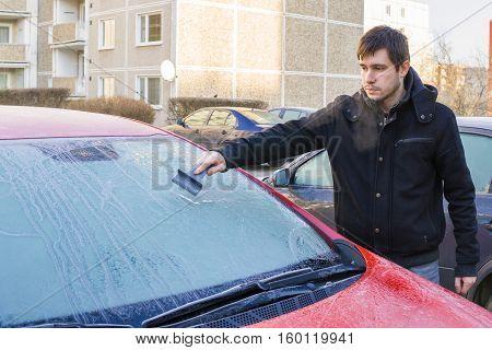 Man Is Scraping Ice From Frozen Windshield Window Of Car In Wint