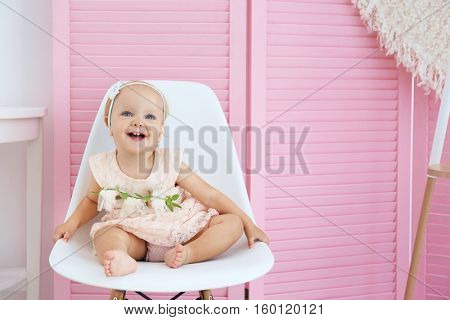 Little baby girl sitting on chair on pink wooden screen background