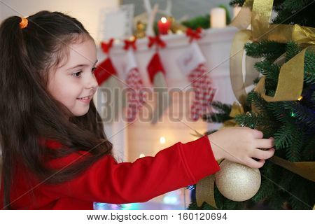 Little girl decorating Christmas tree, on blurred background