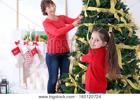 Little girl with her grandmother decorating Christmas tree