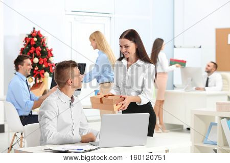 Young woman giving Christmas present to her colleague in office