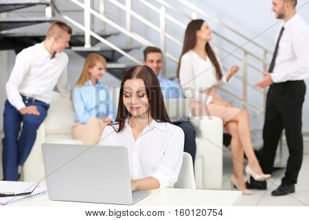 Beautiful young woman working with laptop in office