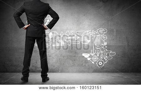Back view of confident businessman in empty concrete room