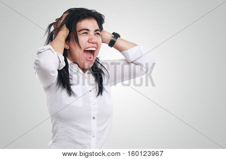 Photo image portrait of a stressed young Asian businesswoman looked so frustrated big mouth screaming while holding hairs on her head side view half body close up portrait