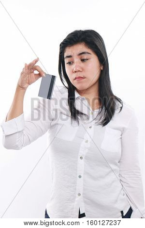 Photo image portrait of a sad Asian woman while looking to her credit card economic depression bankruptcy concept close up portrait over white background