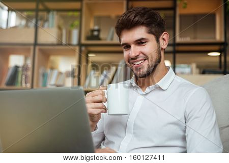 Cheerful businessman dressed in white shirt sitting in cafe and drinking tea while looking at laptop.