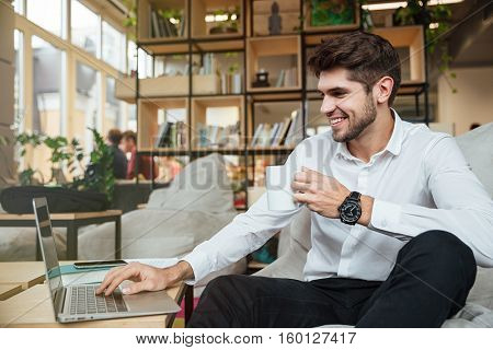 Cheerful businessman dressed in white shirt sitting in cafe drinking tea while looking at laptop.