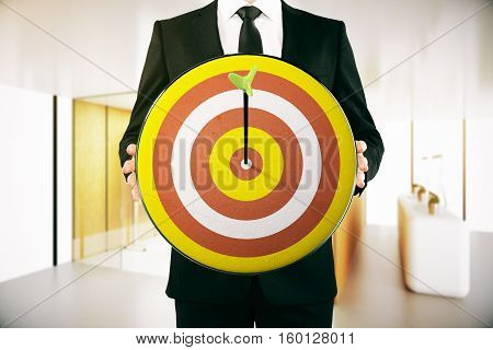 Businessman holding dartboard with arrow in the middle. Modern interior background. Aiming concept. 3D Rendering