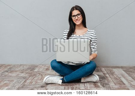 Young cheerful woman wearing eyeglasses sitting on floor while using laptop. Looking at camera.