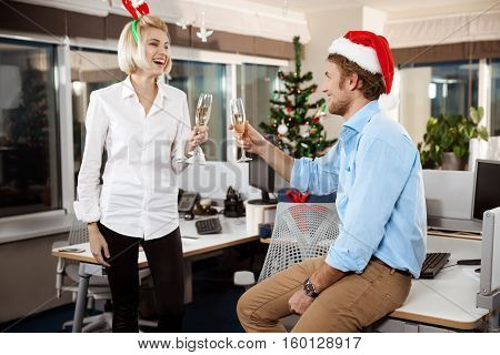 Colleagues celebrating christmas party in office drinking champagne smiling speaking. Copy space.