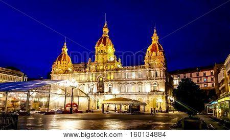 Night cityscape of Coruna, Galicia, Spain. Illuminated Municipal Palace and City Hall Square of Coruna at blue evening hour