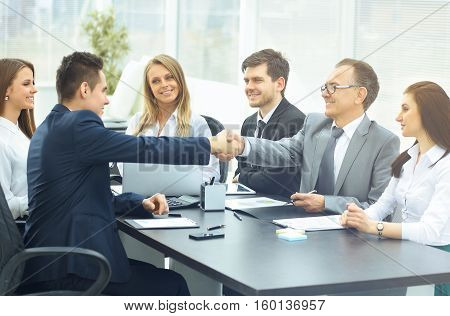 greeting business counterparts in the office behind a Desk