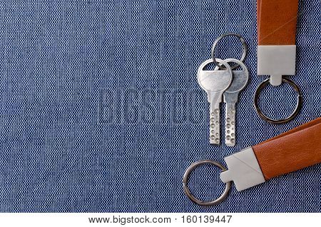Leather key chain with keys on blue fabric background