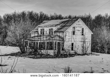 abandoned home with a sagging veranda in black and white