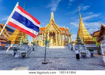 Asian woman praying with Wat phra kaew and thai flag foreground in sunshine day Bangkok Thailand
