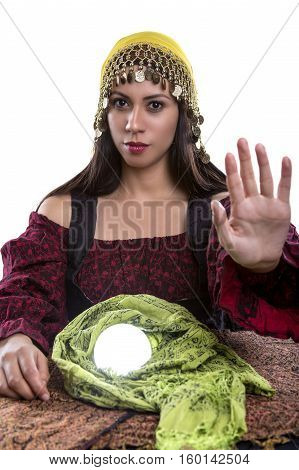 Female psychic or fortune teller with her hands up telling viewer to stop or rejecting. She is isolated on a white