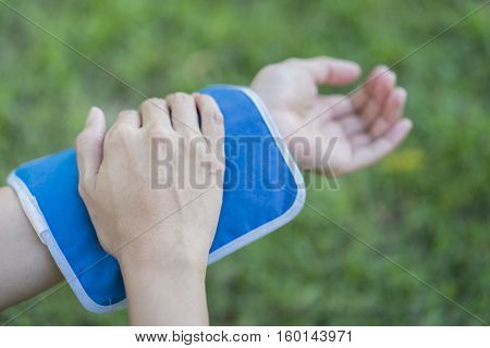 woman putting an ice pack on her arm pain