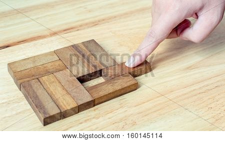 Hand push last piece of wood block to complete the unity metaphor to key to success.
