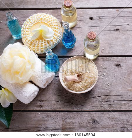 Spa or wellness setting in blue yellow and white colors. Bottles wih essential aroma oil towels candles and wispes on wooden background. Selective focus. Square image.