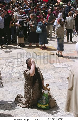 JERUSALEM - APRIL 21: Pilgrim prays on his knees, after a Crucession, in front of Temple, on Good Friday April 21, 2006 in Jerusalem, Israel.