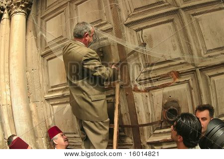 JERUSALEM - APRIL 21: Member of family, that stores the keys of the Holy Sepulchre, open the door to the Holy Sepulchre, on Good Friday April 21 2006