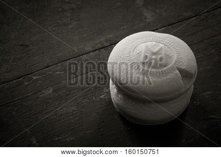 Theotokion service unleavened bread taken out with a particle for Eucharist in the Orthodox Church on the old black wood background with copy space close-up. black and white photo