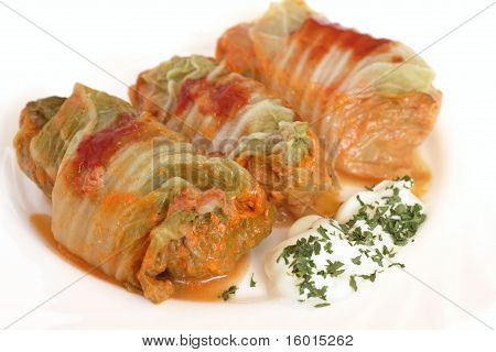Three stuffed cabbage with tomato sauce on a white plate