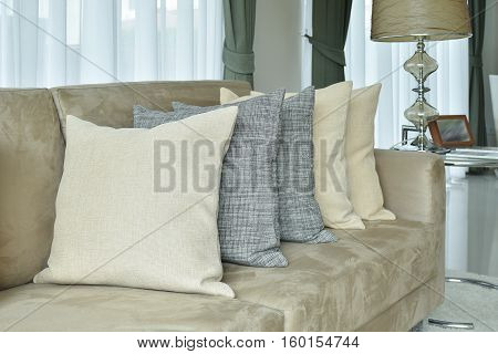 Earth Tone Pillows Setting On Light Brown Sofa In The Living Room