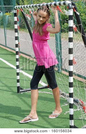 naughty girl at the gate on the football field