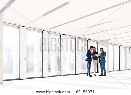 Full length of business people using digital tablet in new office