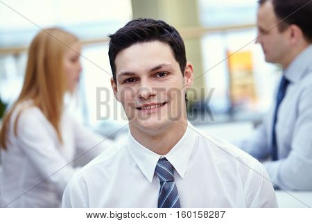 portrait of office worker, his colleagues behind him