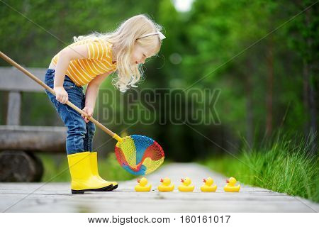 Funny Little Girl Playing With Five Rubber Ducklings