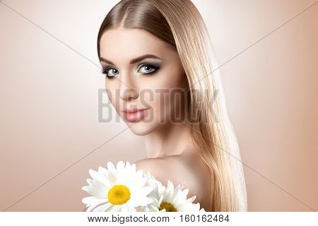 Portrait Of A Young Attractive Girl With A Beautiful Make-up And Perfect Hair On A Beige Background.