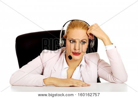 Young woman helpline operator talking through a headphones