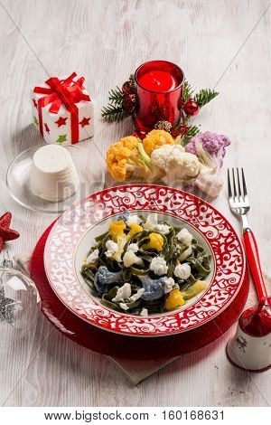 green tagliatelle with cauliflower and ricotta over christmas table