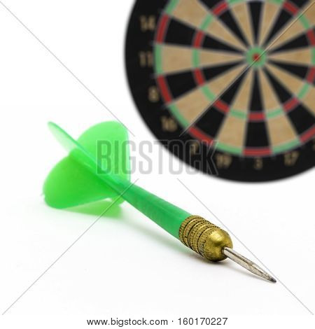 Green dart for dart game on the background of the target.