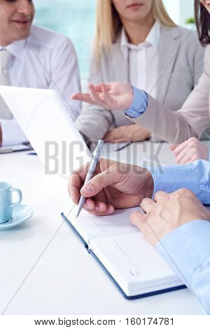 Business people writing something in his notebook