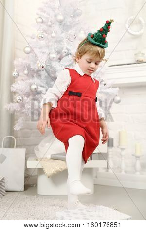 Little girl treading on gift box in front of white christmas tree at home.