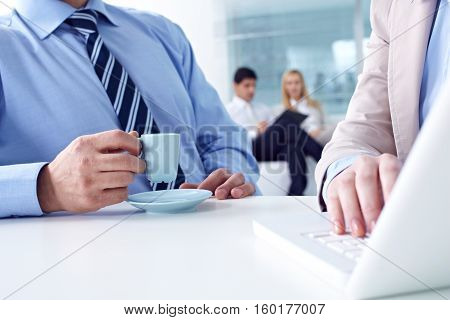 Businessman drinking coffee in office meeting closeup
