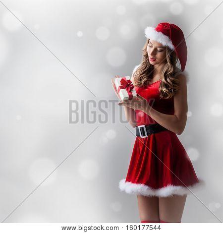 Beautiful hispanic woman in red santa claus costume holding Christmas gift