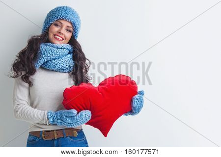 Beautiful smiling brunette woman in winter hat and scarf holding a red heart