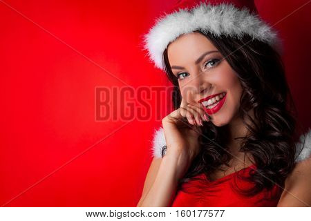 Pretty Pin-up style Santa girl in red hat on red background