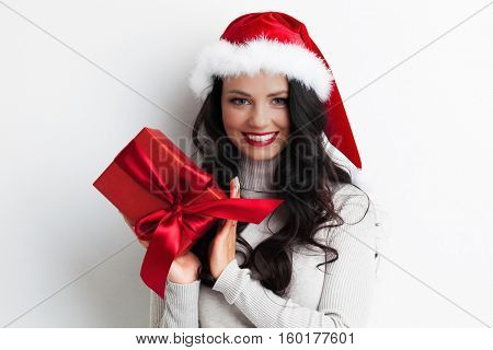 Young happy woman in santa hat holding christmas gift box