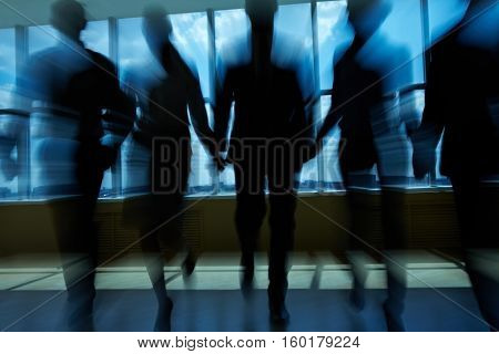 Silhouettes of people in office going ahead