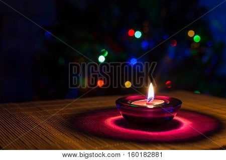Christmas holiday background with purple tea candle and colorful lights of Christmas tree with copyspace