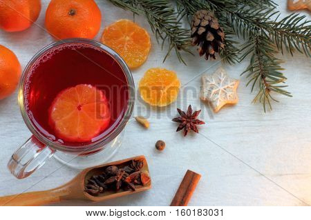 mulled wine in a transparent mug with mandarin oranges spices and ginger cakes figured top view / festive table for winter holidays