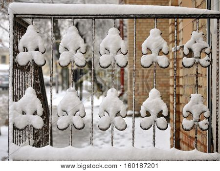 Vintage metal wrought iron fence covered with snow after a snowfall.