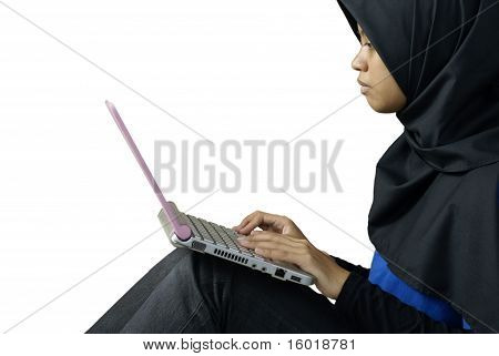 Serious muslim asian lady using laptop