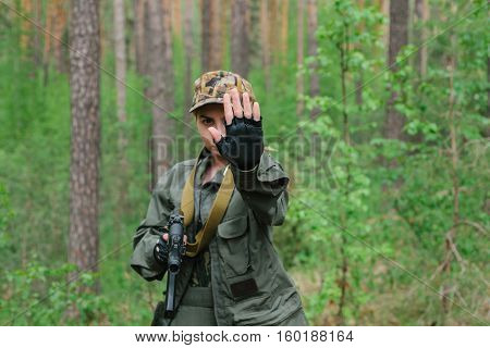 A woman soldier with a weapon shows a hand stop.