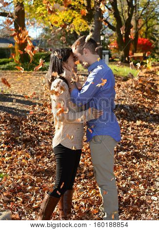 Young attractive couple in love in an autumn setting following their engagement looking at each other with leaves falling around them